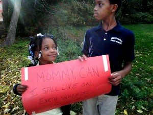 "Kids hold a sign that reads ""Mommy, can I still live on Earth when I grow up?"""