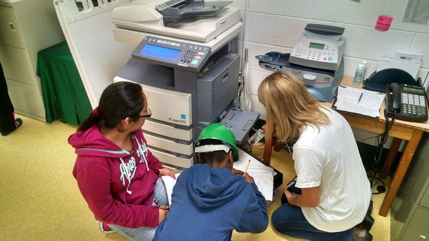 Sixth graders measure how much energy a copier uses in an energy audit with Repower Our Schools.