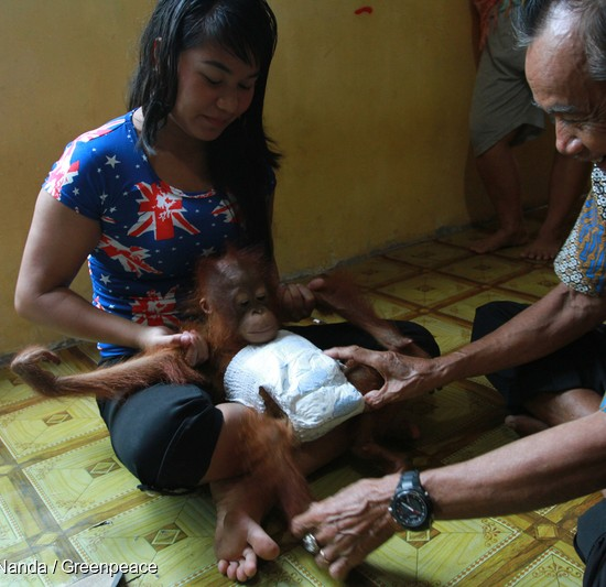 Ayu and her father-in-law play with baby Otan.