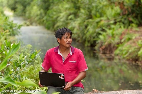 Pak Manan holding his laptop, which has the digital maps of Sungai Tohor forest that was burned in 2014.