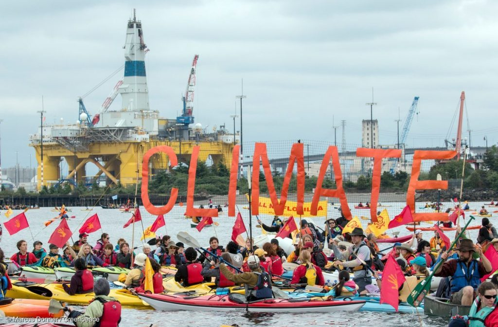 "Activists raise a ""Climate"" banner in the sHell No Flotilla in the 'Paddle in Seattle' protest."