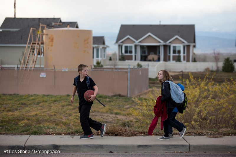 Children walk to school past a tank being used in oil and gas production in Weld County, northern Colorado, the most intensively fracked area in the United States.