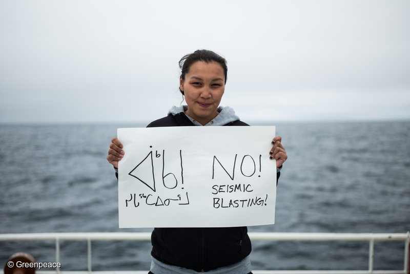 Resident of Clyde River, Clara Natanine stands on the deck of the Arctic Sunrise with an anti-seismic blasting sign that she made herself. Arctic Sunrise crew and guests set travel through the Davis Straight. The ship is bound for Clyde River, Nunavut, where she will deliver solar panels for the community.