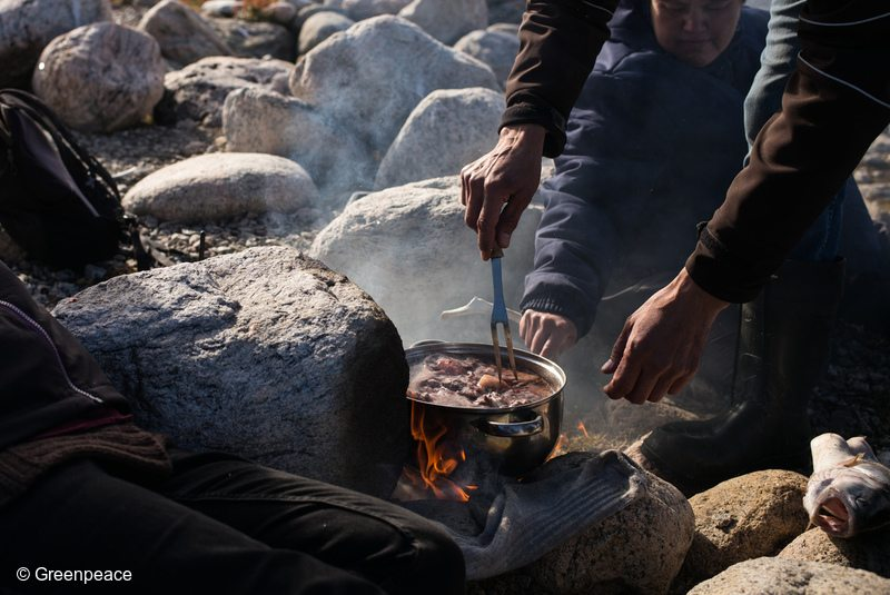 Former mayor of Clyde River, Jerry Natanine and his wife Christine cook up a pot of seal meat, during a picnic of country foods, near Clyde River. Greenpeace has come to deliver solar panels and offer a series of lectures and workshops in Clyde River.
