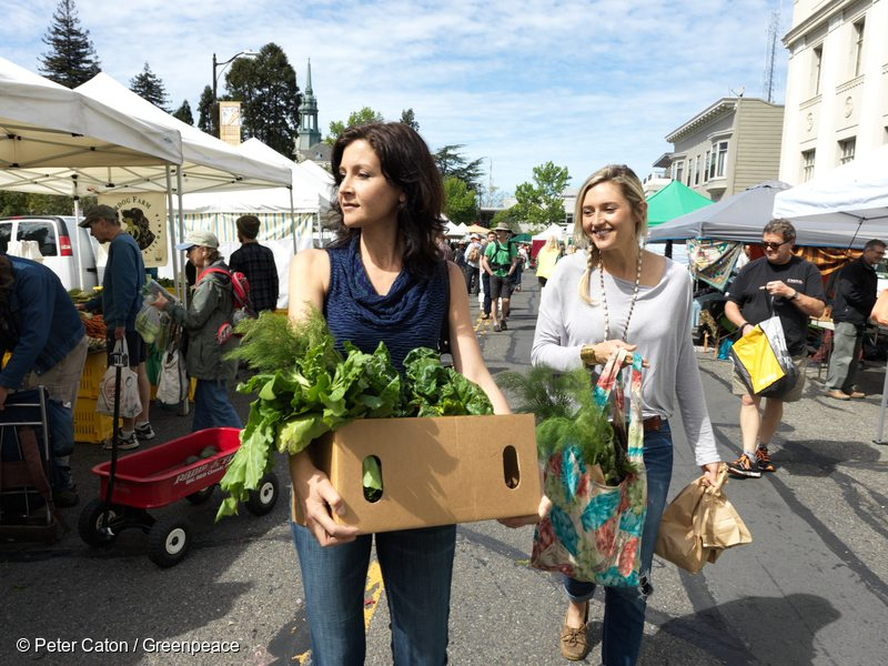 Britney Barret, a chef, and her friend Amy buy fresh ecological produce at a farmers market in Berkeley, California.