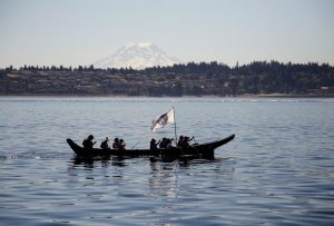 """A crew pulls their canoe in the Salish Sea (Puget Sound) on the 2016 Canoe Journey """"Paddle to Nisqually."""" Mt. Rainier is in the distance."""