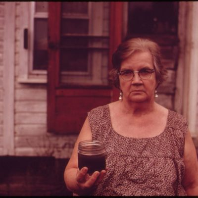 Mary Workman Holds A Jar of Undrinkable Water That Comes from Her Well