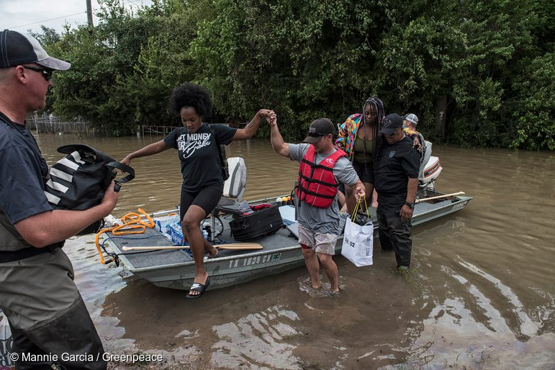 People with their personal boat help rescue residents from flooded neighborhoods near Katy, Texas.