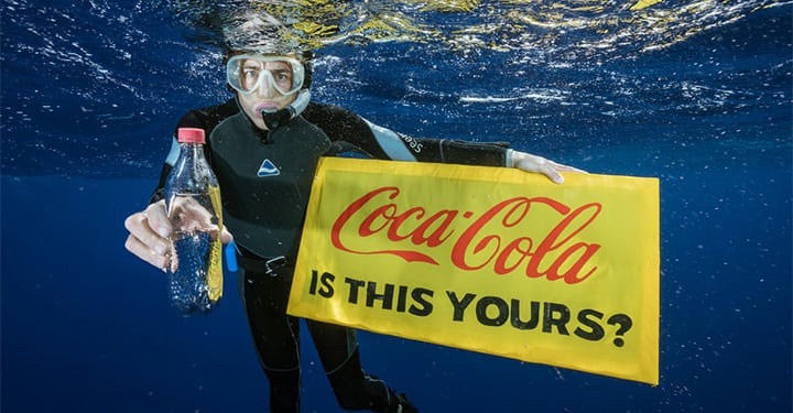 "A Greenpeace diver holds a banner reading ""Coca-Cola is this yours?"" and a  Coca-Cola bottle found adrift in the garbage patch.   The crew of the Greenpeace ship MY Arctic Sunrise voyage into the Great Pacific Garbage Patch document plastics and other marine debris. The Great Pacific Garbage Patch is a soupy mix of plastics and microplastics, now twice the size of Texas, in the middle of the North Pacific Ocean."