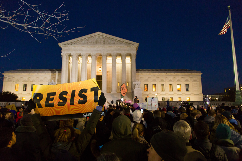 """A photo showing a crowd of people protesting at night outside of the US Supreme court. In the foreground, there is a person holding a sign that reads """"RESIST."""""""