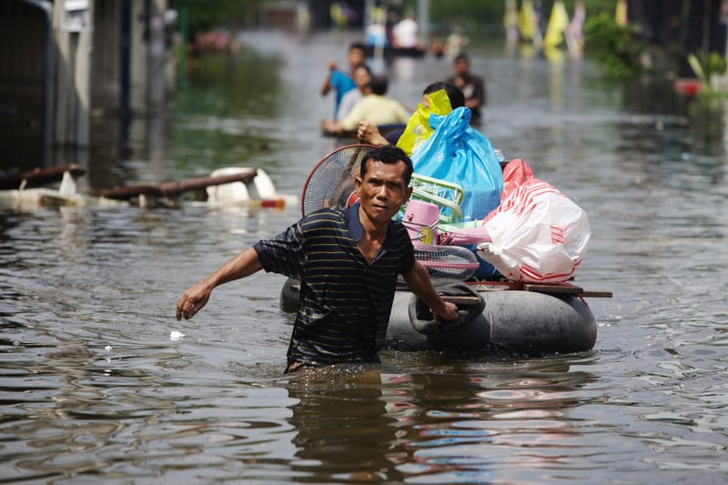 A man floats his possessions down a flooded street in Bangbuathong area, Nonthaburi province, on the northern outskirts of Bangkok. In 2011, Thailand had the worst flooding in five decades, which killed hundreds of people and affected millions more who have had to flee their homes.