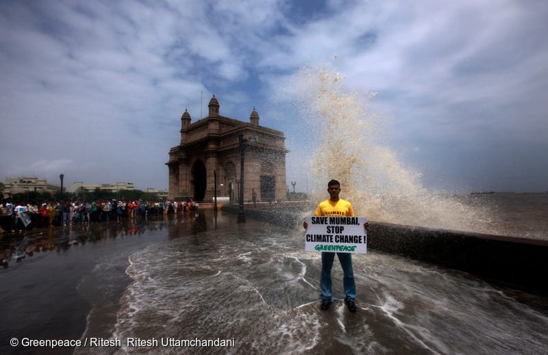 "An activist holds a banner reading ""Save Mumbai Stop Climate Change"". One of the highest tides in a hundred years batters the Mumbai coast. The city is going to be hard hit by climate change and sea level rise according to a recent World Bank report."