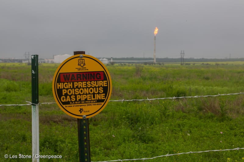 A sign on a fence line near Westhoff warning about the danger of a high pressure gas pipeline at the site. Gas is burned off at the flare in the background at an Eagle Ford shale fracking installation in DeWitt County.