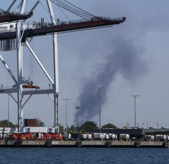 Smoke rises from an area believed to be in the vicinity of oil refineries during a tour of the fossil fuel infrastructure in the ports of Long Beach and Los Angeles to demonstrate the health and environmental justice impacts on local communities.