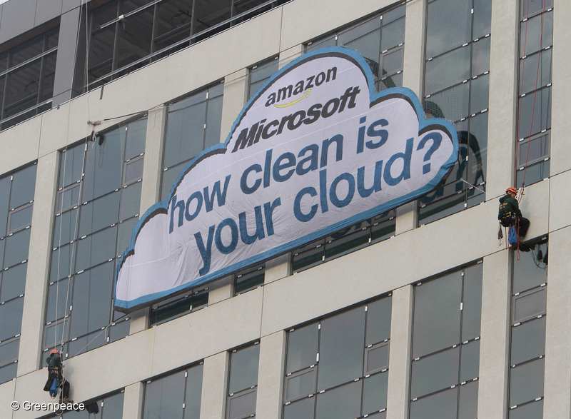 Greenpeace activists hang a cloud-shaped banner outside of Amazon.com's headquarters, and across the street from Microsoft offices, reading