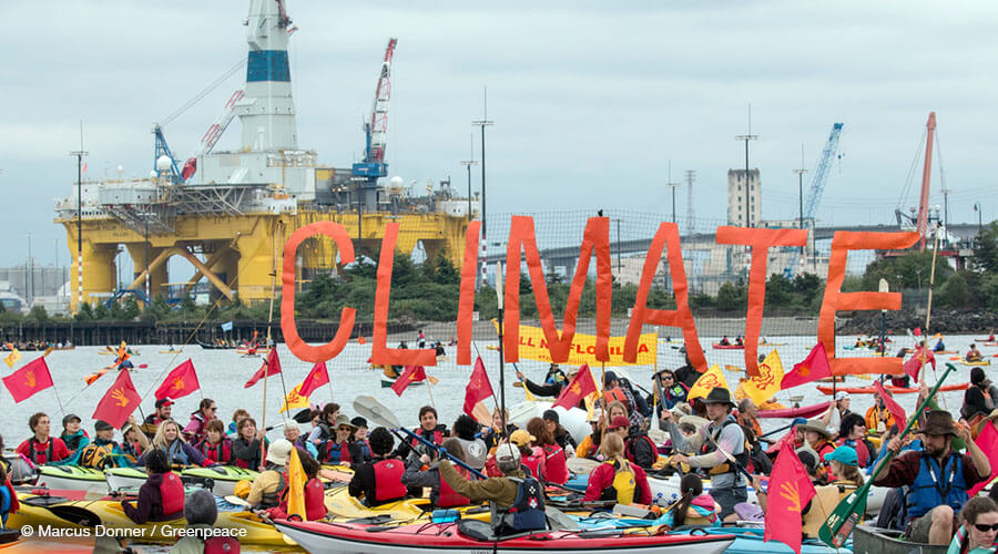 "Activists raise a ""Climate"" banner in the sHell No Flotilla in the 'Paddle in Seattle' protest"
