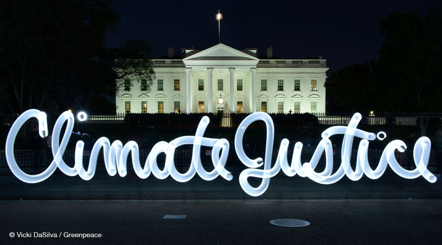 "Light graffiti reading ""Climate Justice"" in front of the White House"