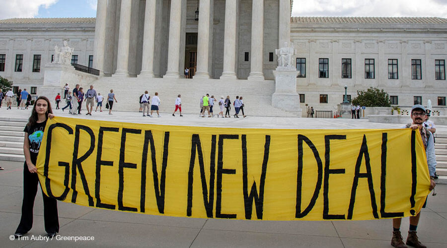 Student activists hold up a Green New Deal sign in front of the US Supreme Court following the press conference.