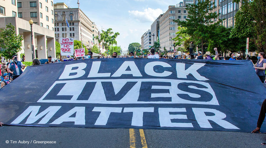 Greenpeace US activists walk a large Black Lives Matter banner down 16th NW toward the White House
