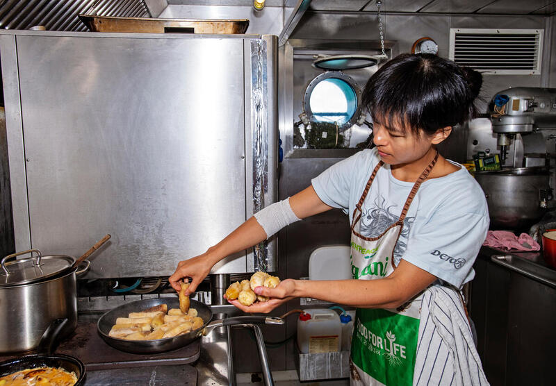 I'm assisting our Chef Laurence by frying bananas in the galley on board the Rainbow Warrior in the Pacific. © Marten van Dijl / Greenpeace