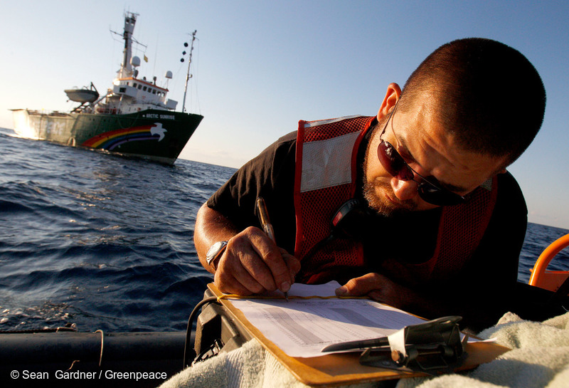 PHOTO: DOER Supervisor Rudy Schlepp writes in the dive log of the Dual Deep Worker submarine on an inflatable boat near the Greenpeace ship MY Arctic Sunrise in the Gulf of Mexico. A team of independent scientists joined the crew of the Arctic Sunrise to conduct a series of scientific research programs that will further the understanding of the impacts of both oil and chemical dispersant on the Gulf ecosystem in the aftermath of the British Petroleum oil spill.
